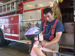 fireman fitting helmet on child